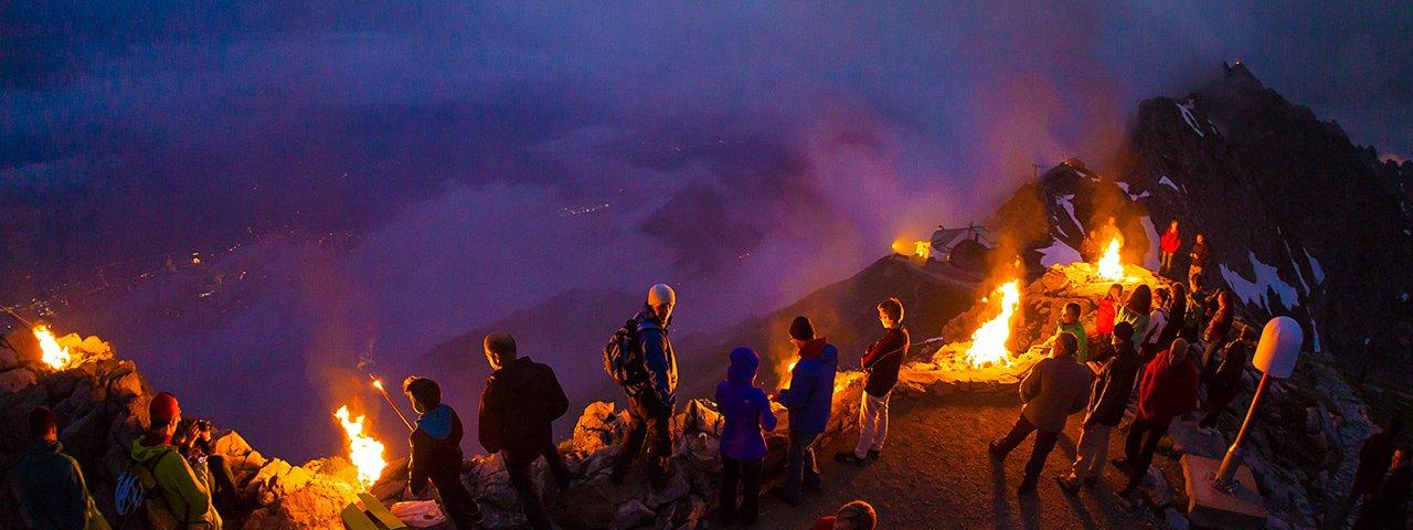 Plechtige sfeer bij de zonnewende-bergvuren op de Nordkette hoog boven Innsbruck, © Webhofer / W9 Werbeagentur